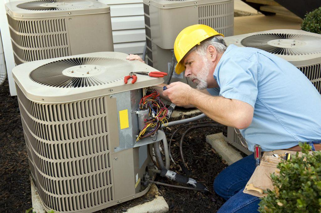 old man repairing the AC