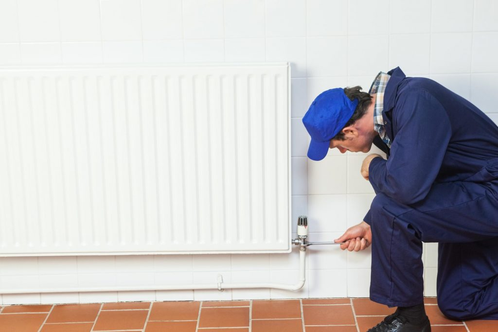 man repairing the heater